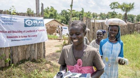 Vrouwen dragen spullen vanuit het dorp.