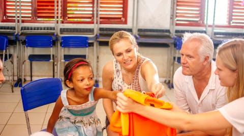 Sarina laat een oranje voetbalshirt zien aan een van de kinderen.
