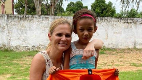 Sarina poseert met een oranje voetbalshirt en een van de kinderen.