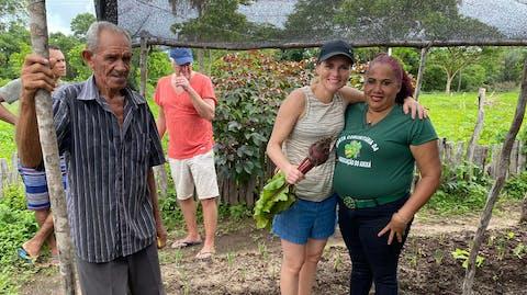 Sarina met een paar werkers in de tuin.