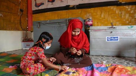 meisjes spelen met kralen in opvangcentrum van Plan International