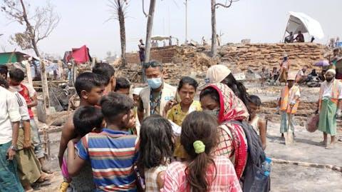 Plan medewerker helpt vluchtelingen in kamp Cox's Bazar Bangladesh