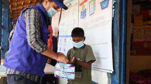 Plan International medewerker helpt jongen noodhulp bangladesh