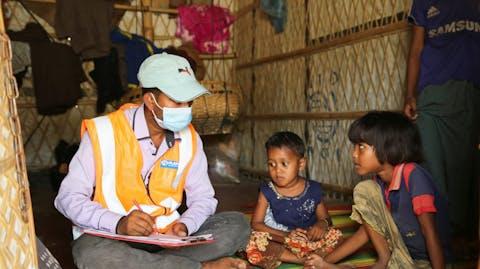 Plan medewerker helpt kinderen hun ouders te vinden in vluchtelingenkamp Cox's Bazar Bangladesh