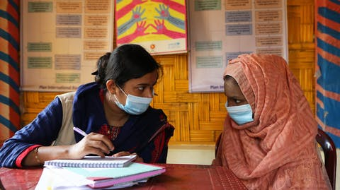 Plan medewerker helpt Rohingya vluchteling in noodcentrum Cox's Bazar bangladesh